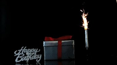 Sparkler burning beside gift and happy birthday sign — Stock Video