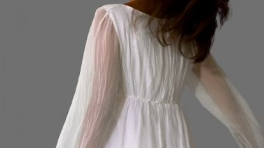 Girl in white dress twirling on grey background close up — Stock Video