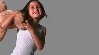 Little girl twirling and catching teddy on grey background — Stock Video