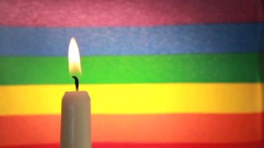 Candle against rainbow flag — Stock Video