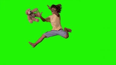 Little boy jumping up and catching teddy bear on green screen — Stock Video