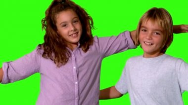 Brother and sister jumping into same shot and embracing on a green screen — Stock Video