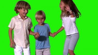 手牵着手和绿色屏幕上跳跃的兄弟姐妹 — 图库视频影像
