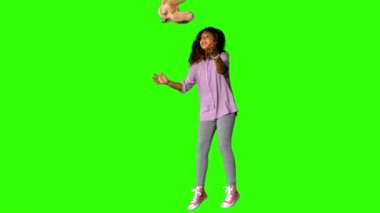 Happy little girl jumping up and catching teddy on the green screen — Stock Video