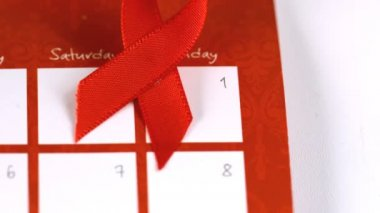 Red ribbon symbol for Aids falling on a calendar — Stock Video #25671733