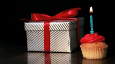 Candle on cupcake blown beside gift — Stock Video