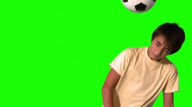 Boy heading a football on green screen — Stock Video
