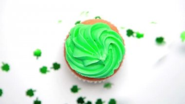 St patricks day cupcake revolving with green shamrock confetti falling — Stock Video