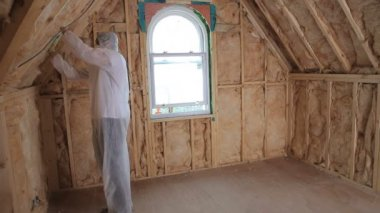 Builder in protecive suit insulating house — Stock Video