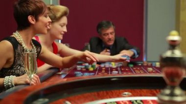 Women putting chips on table — Stock Video