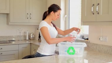 Woman putting bottles into recycling bin — Stock Video