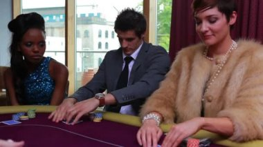 Being dealt poker cards with two folding and one placing bet in the casino