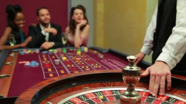 Casino dealer spinning the roulette wheel