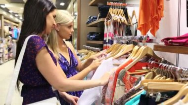 Women looking through clothes rail — Stok video