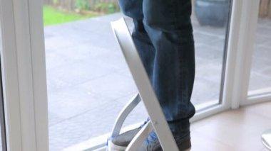 Man standing on a ladder fixing light — Stock Video