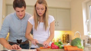 Woman cutting vegetables with man reading cookbook — Stock Video