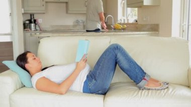 Pregnant woman relaxing on sofa with book — Stock Video