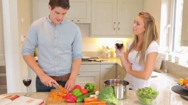 Man is cutting vegetables with woman drinking wine then kissing — Stock Video