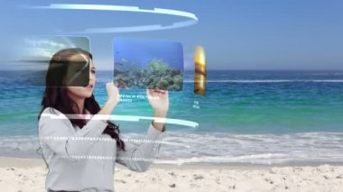 Woman looking at holiday activities on interactive media library on beach — Stock Video