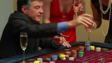 Man smoking a cigar wins at roulette in the casino