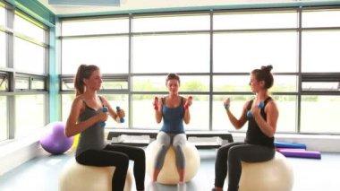 Kvinnor sitter på träningsbollar lyfta vikter — Stockvideo