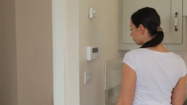 Woman turning on alarm system — Stock Video