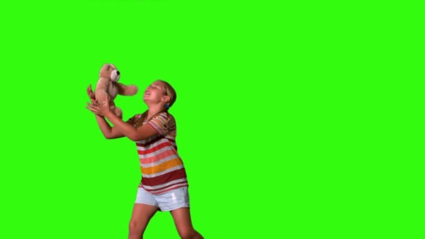 Girl jumping and catching teddy on a green screen — Vidéo