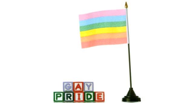 Bandera del arco iris soplando en el viento al lado de los bloques del orgullo gay sobre fondo blanco — Vídeo de stock