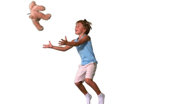 Boy jumping and catching teddy bear on white background — Vidéo