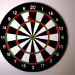 Dart hitting dart board beside another dart — стоковое видео #25683855