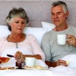 Mature couple enjoying breakfast in bed — Stock Video