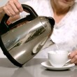 Woman pouring hot water from kettle into cup — Stock Video