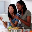 Stock Video: Young women following online recipe on tablet pc