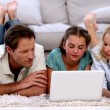 Parents and daughter happily using laptop on floor — Stock Video #25687997