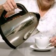 Stock Video: Woman pouring boiling water from kettle into cup