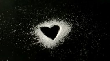 Heart drawn into sugar being blown out by wind — Stock Video