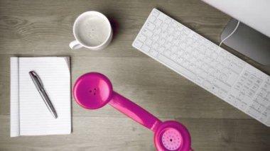Récepteur téléphone rose tombant sur le bureau — Vidéo