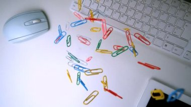 Colourful paperclips falling in the middle of a white office desk — Stock Video