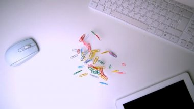 Colourful paperclips falling on office desk — Stock Video