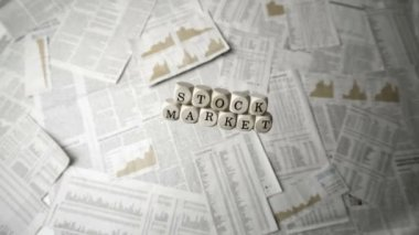 White dice spelling out stock market falling over sheets of paper — Stock Video