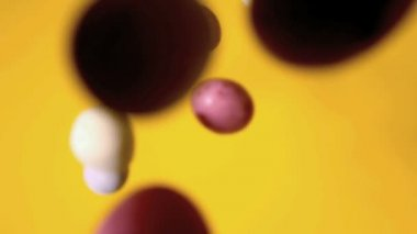 Ostereier auf gelbe fläche fallen — Stockvideo