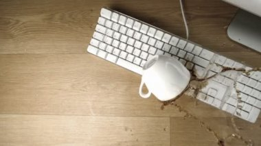 Cup of tea spilled out over a white keyboard — Stock Video