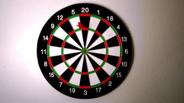 Dart hitting the dart board beside another dart — Стоковое видео