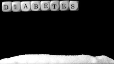 Diabetes de ortografía dados blanco cayendo sobre un montón de azúcar — Vídeo de stock