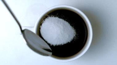 Teaspoon pouring sugar into cup of coffee — Stock Video