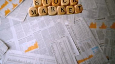 Wooden dice spelling out stock market falling over sheets of paper — Stock Video