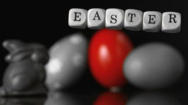 Dice spelling out easter falling in front of easter treats and egg black and white — Stock Video