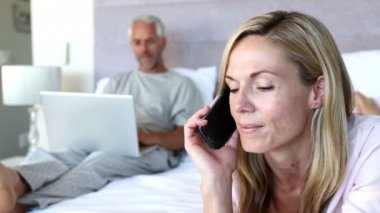 Woman laughing while she is on the phone next to his husband on his laptop — Vídeo de stock