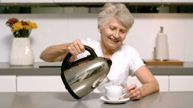 Retired woman pouring boiling water from kettle into cup — Stock Video