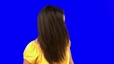 Smiling woman tossing her hair on blue screen — Stock Video